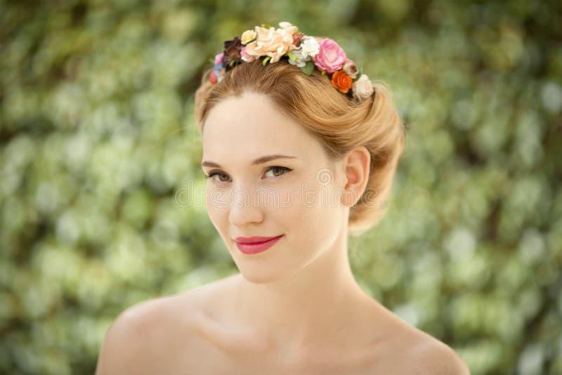 有花的美丽的少妇在头发缠绕 库存图片