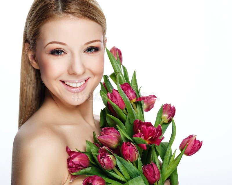 有花的美丽的微笑的白肤金发的妇女 免版税库存图片