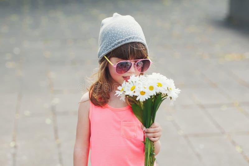 有花的美丽的矮小的行家女孩 库存图片