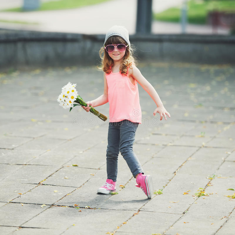 有花的美丽的矮小的行家女孩 图库摄影