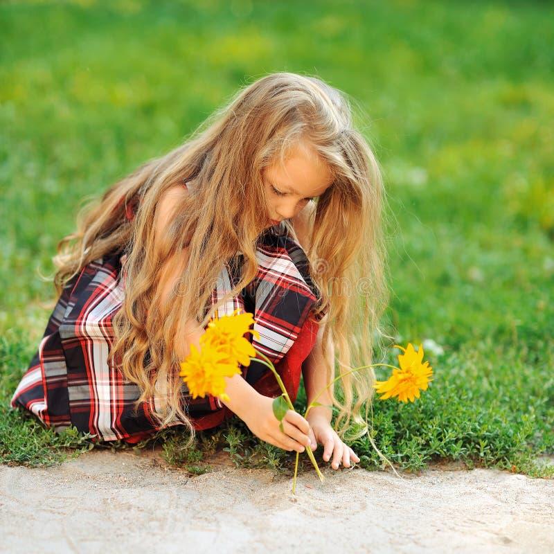 有花的逗人喜爱的小女孩在夏天津贴 图库摄影