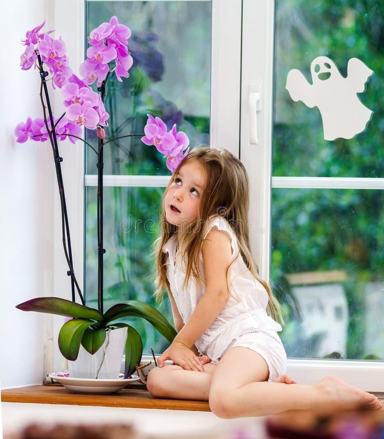 有花的逗人喜爱的小女孩坐新的pvc wi窗台  免版税库存图片