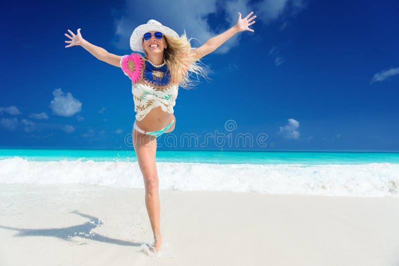 有花的长发白肤金发的妇女在比基尼泳装的头发在热带海滩 免版税图库摄影