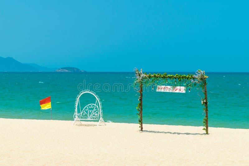 有花的门与白色摇摆和旗子在海滩在海岛上 免版税库存照片