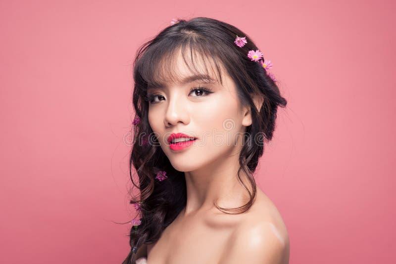 有花的年轻人相当亚裔妇女在头发关闭在桃红色b 库存照片