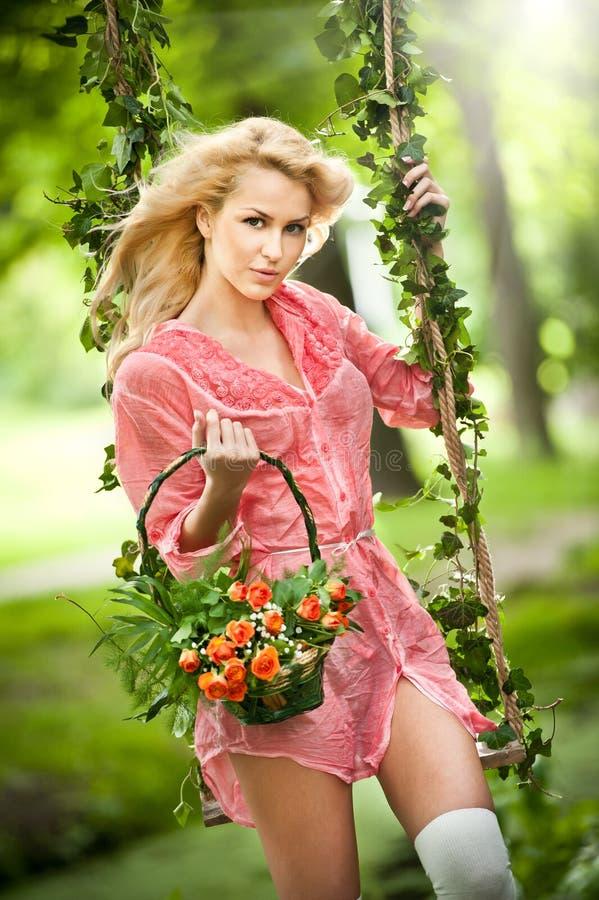 有花篮子的美丽的金发碧眼的女人在叶茂盛摇摆 免版税库存照片