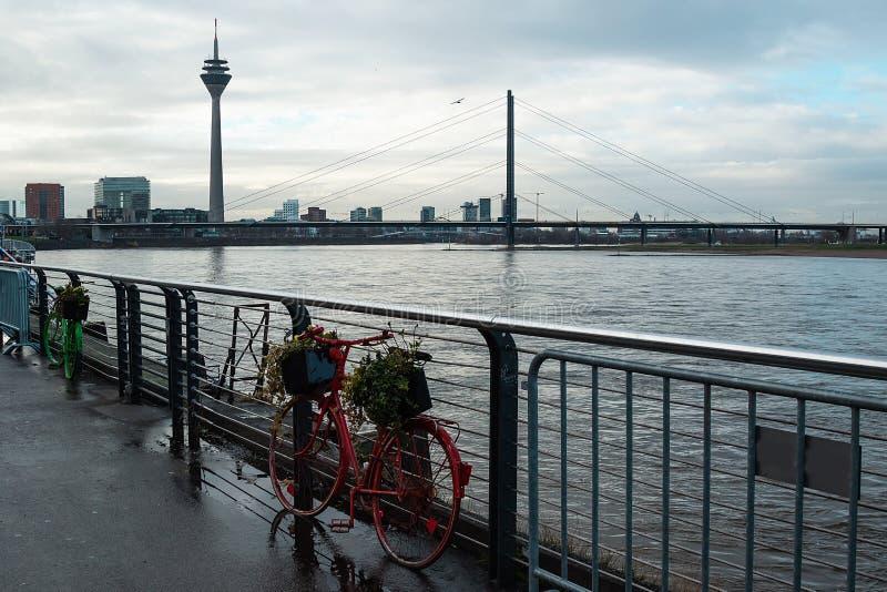 有花篮子的色的自行车在堤防的在电视塔的背景,桥梁在雨中 免版税库存图片