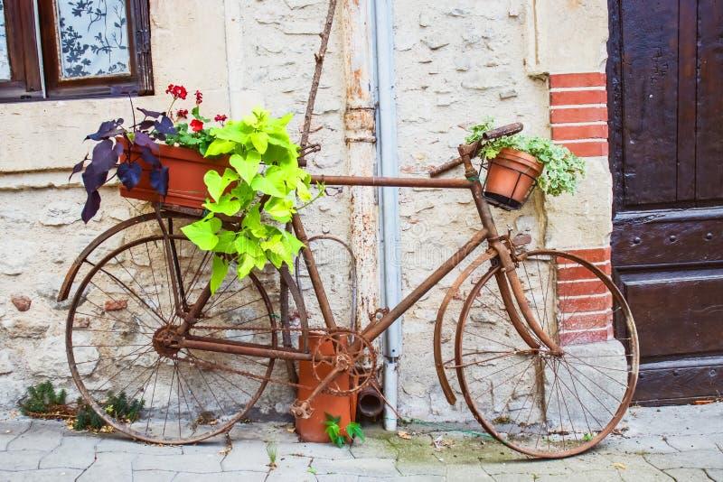 有花篮子的葡萄酒自行车在老土气房子前面的在法国,欧洲 免版税库存图片