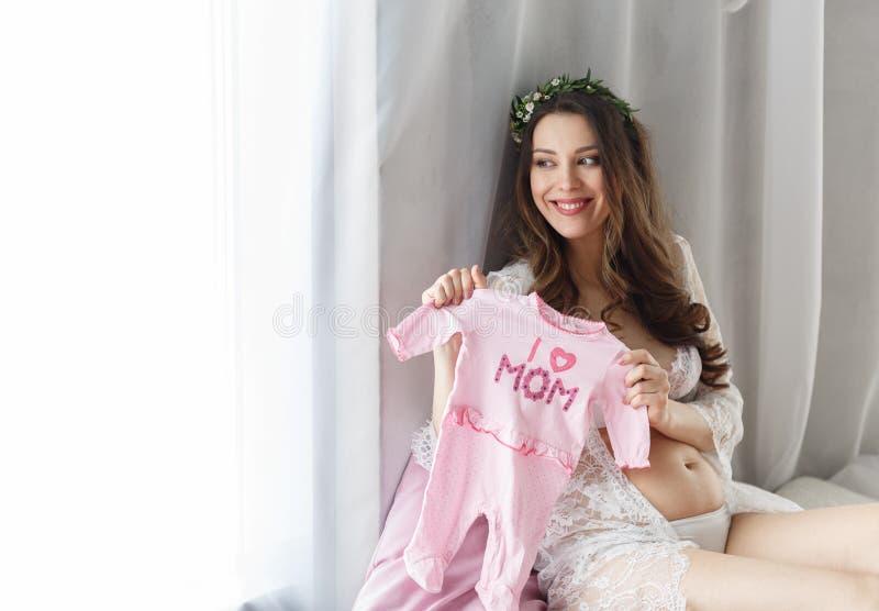 有花花圈的一个美丽的年轻怀孕的女孩在她的头的在有鞋带的一件白色礼服在窗口附近坐和 库存照片