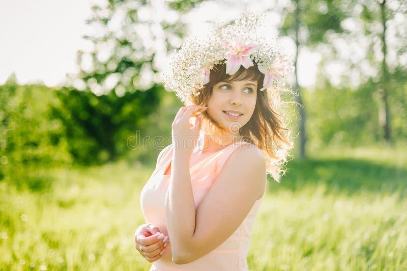 有花花圈的美丽的女孩在她的微笑户外在一个晴天的头的 库存图片