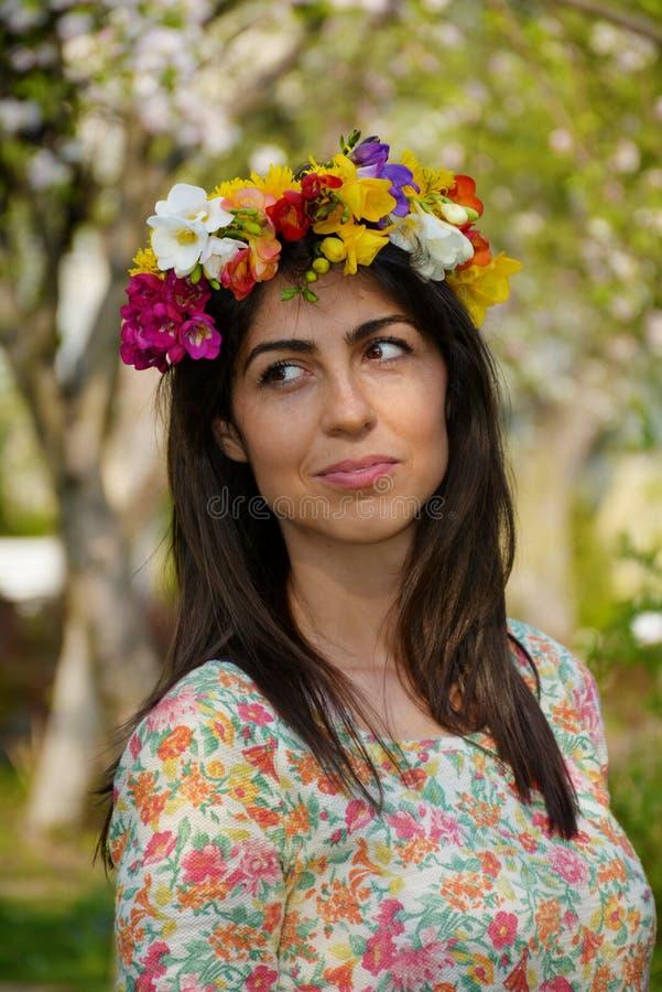 有花花圈的美丽的深色的妇女在春天庭院 免版税库存图片