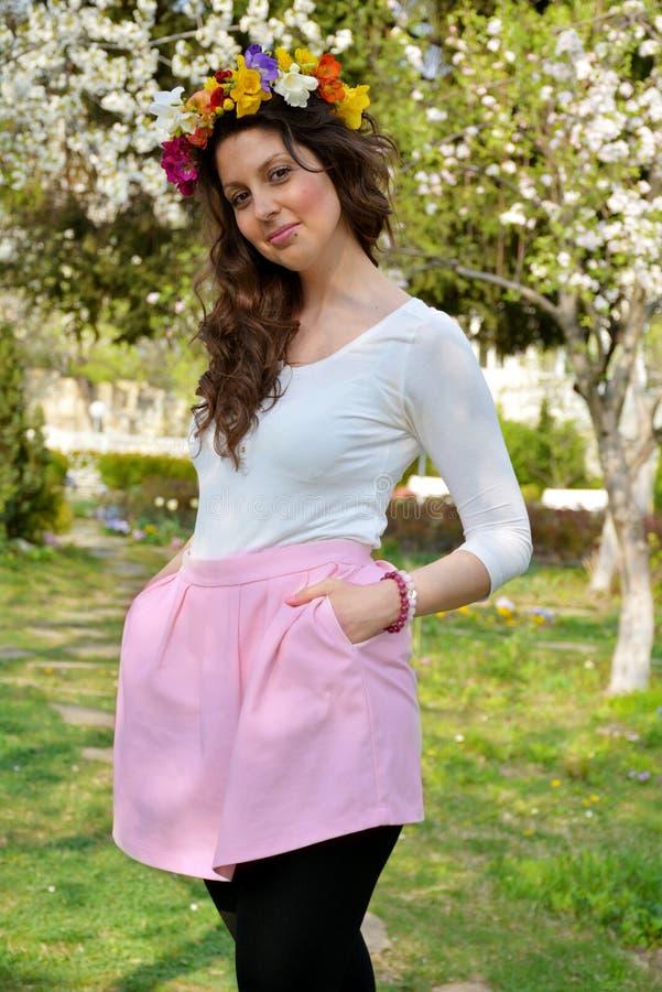 有花花圈的美丽的深色的妇女在春天庭院 免版税库存照片