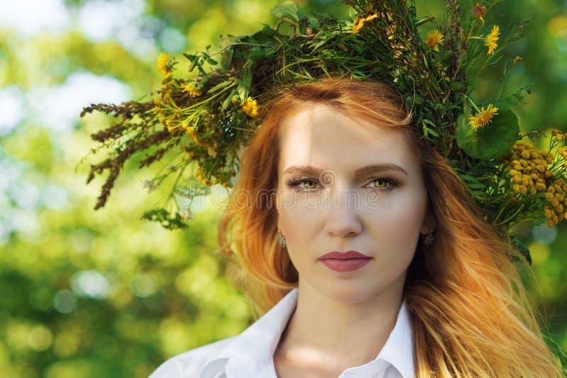 有花花圈的美丽的白肤金发的妇女在头的 免版税库存图片