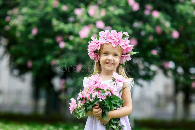有花花圈的逗人喜爱的微笑的女孩在公园 户外可爱的小孩子画象  ?? r 免版税库存照片
