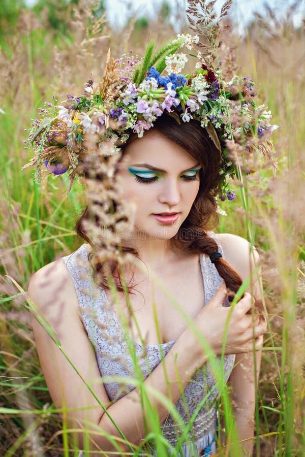 有花花圈的年轻美丽的妇女在草甸 库存图片