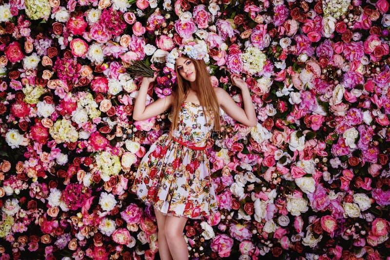有花花束的一个美丽的女孩在花卉墙壁附近 免版税库存照片