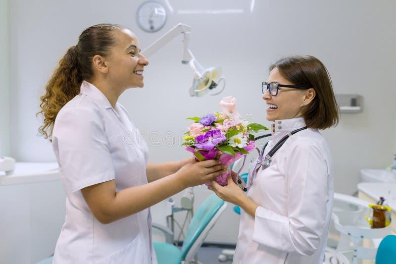 有花花束的两位女性牙医在牙齿办公室 全国医生` s天 库存图片