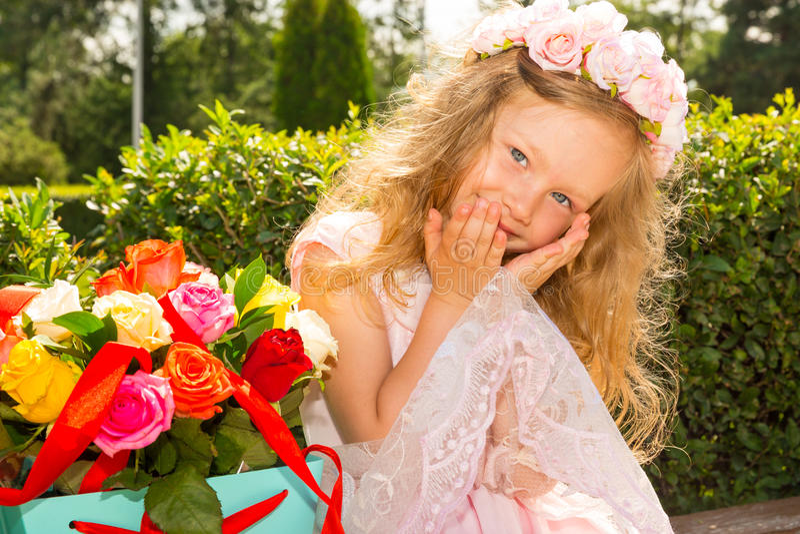有花花束的可爱的小孩女孩在生日快乐 夏天绿色自然背景 免版税库存照片
