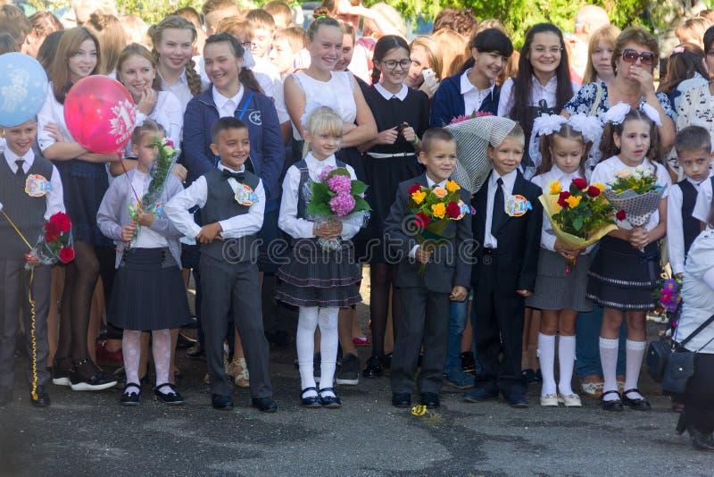 有花花束的孩子在头等注册了在学校在学年的就职典礼在天knowl 免版税库存照片