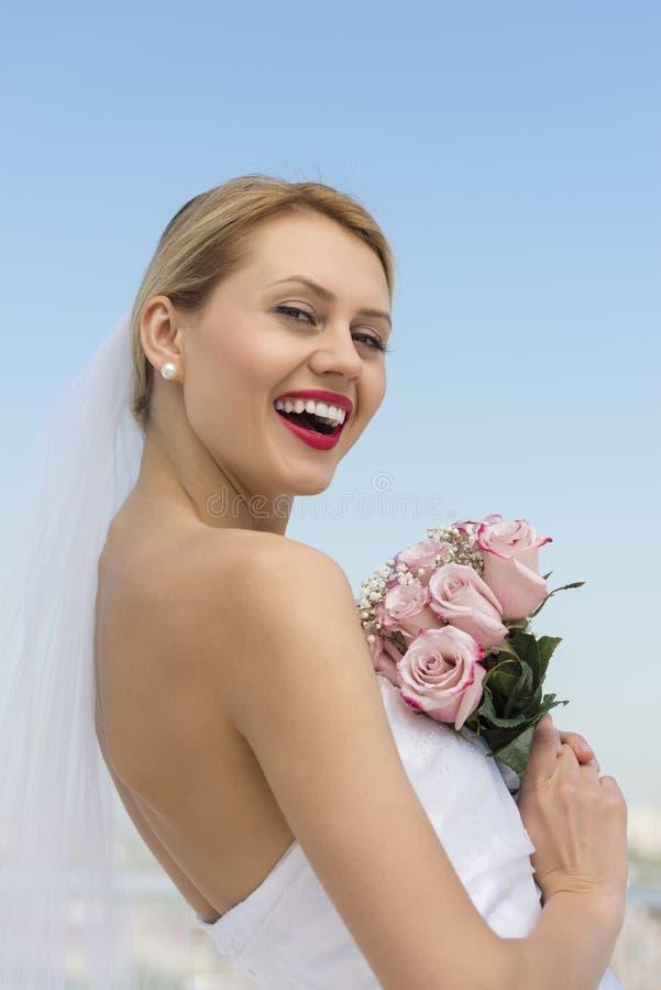 有花花束的快乐的新娘反对清楚的蓝天 免版税库存图片