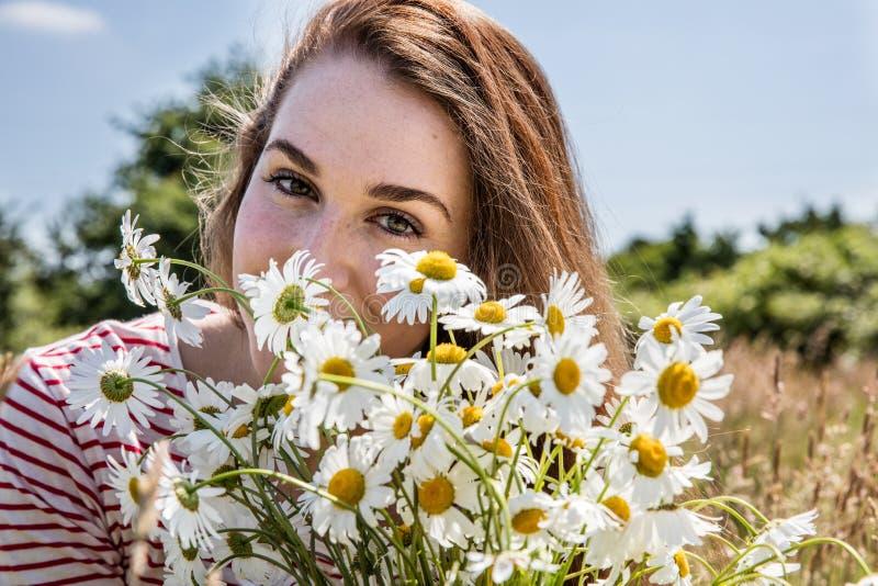有花花束的美丽的少妇微笑为自然秀丽的 库存照片