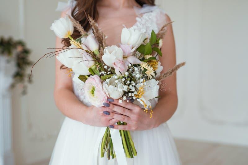 有花花束的美丽的深色的新娘在白色墙壁附近的屋子里 库存照片