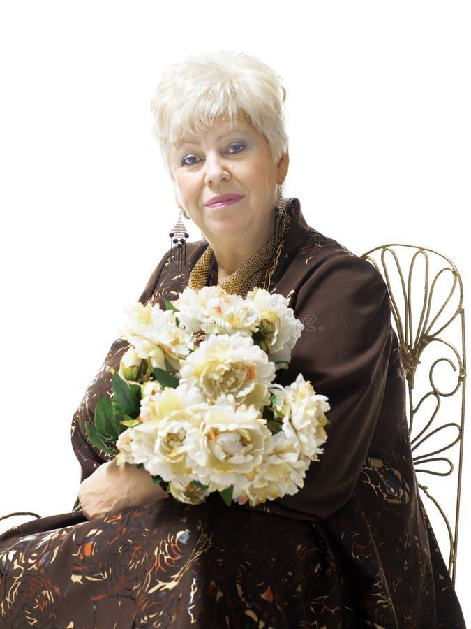 有花花束的美丽的白肤金发的成熟妇女  库存图片