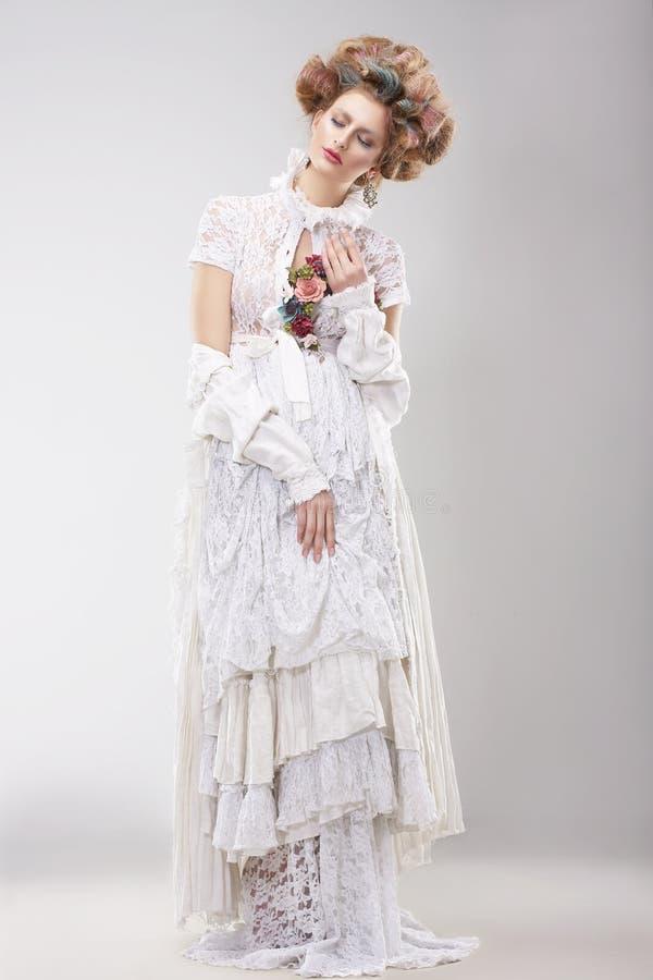 有花边的白色礼服的华美的过度的女性有花的 免版税库存照片