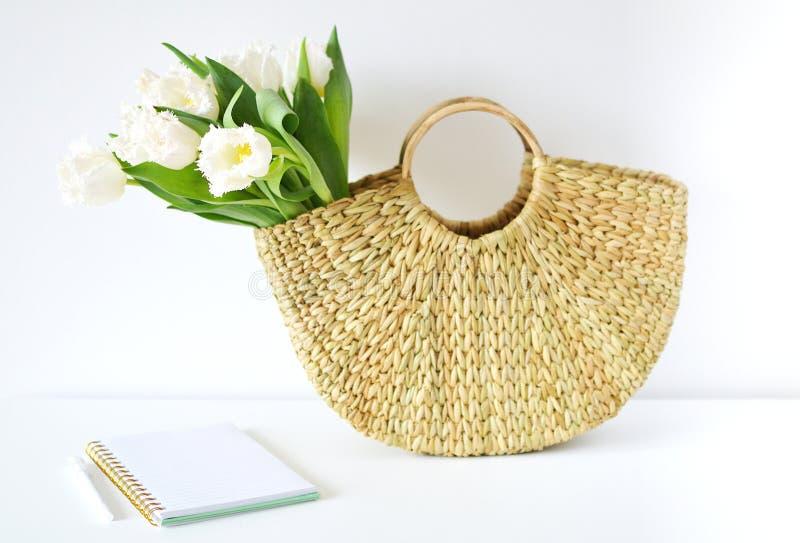有花郁金香的柳条提包,春天,夏天概念 免版税库存照片