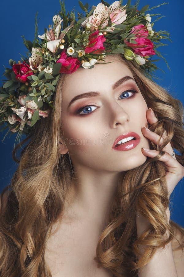有花饰的美丽的女孩在她的在蓝色背景的头发 花妇女花圈 秀丽表面 时尚phot 图库摄影