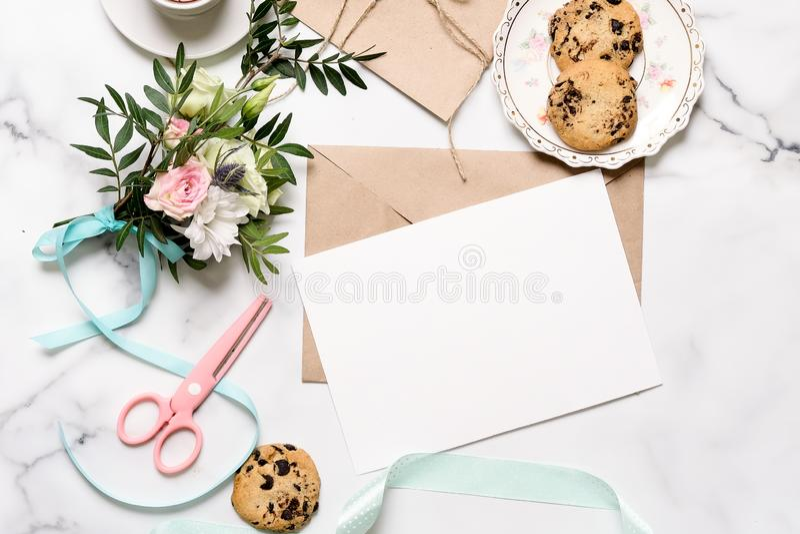 有花,桃红色剪刀,明信片,卡拉服特信封,棉花分支,燕麦曲奇饼,与警察的邀请卡片花束的大理石书桌  免版税图库摄影