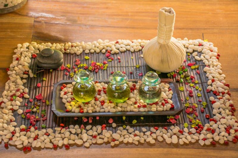 有芳香油和香料的三个玻璃瓶在木桌上 图库摄影
