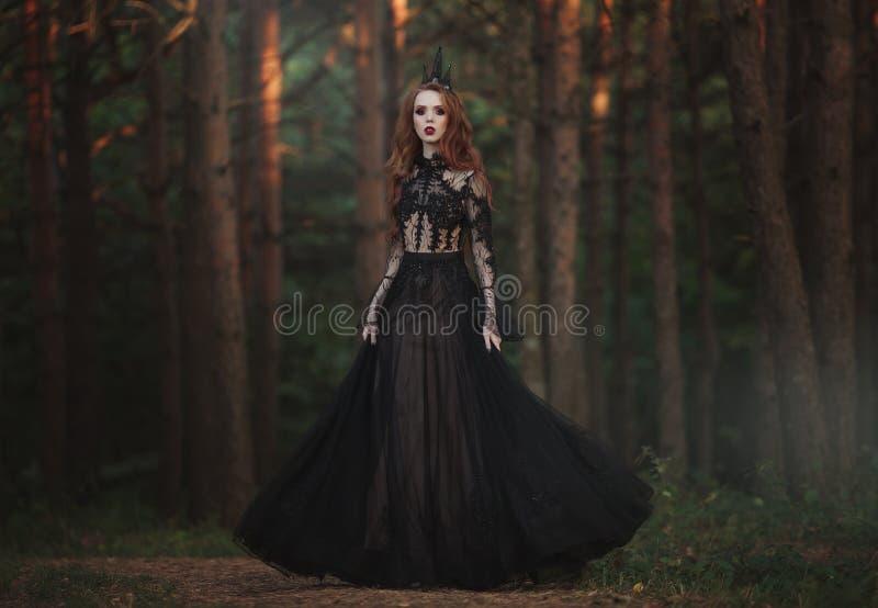 有苍白皮肤和非常长的红色头发的一位美丽的哥特式公主在一个黑冠和一件黑长的礼服在一个有薄雾的神仙的森林里 免版税图库摄影