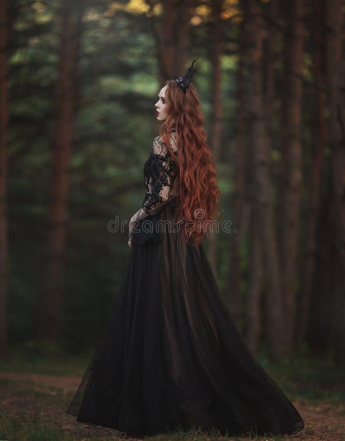 有苍白皮肤和非常长的红色头发的一位美丽的哥特式公主在一个黑冠和一件黑长的礼服在一位有薄雾的神仙t走 免版税库存照片