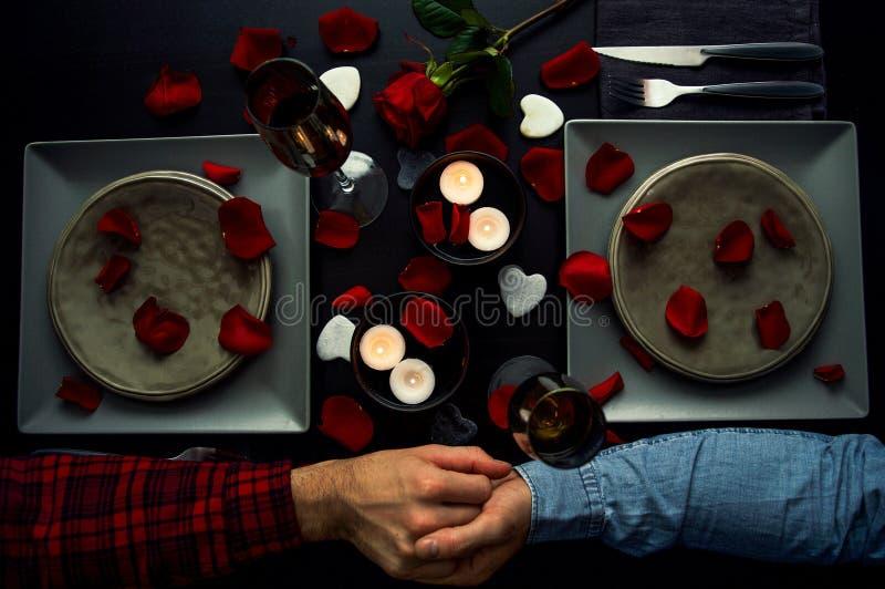 有英俊的年轻的夫妇握手的浪漫吃饭的客人 顶视图 蜡烛、花和酒 库存照片