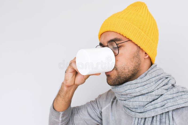 有英俊的男性侧视图喉咙痛流行性感冒 病的人画象食用grippe和水杯茶,戴着眼镜 免版税库存照片