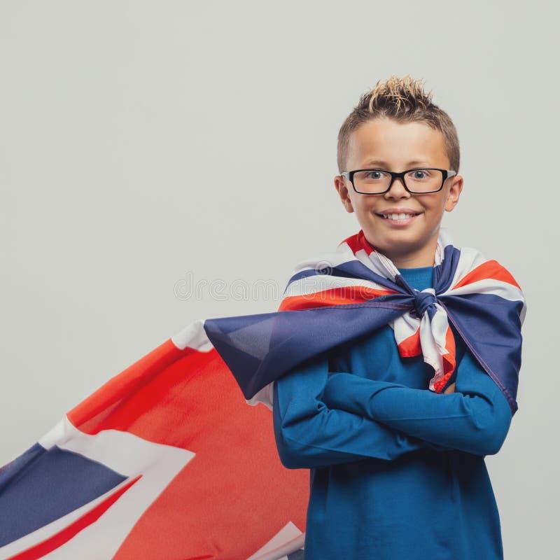 有英国旗子海角的微笑的超级英雄男孩 免版税库存照片