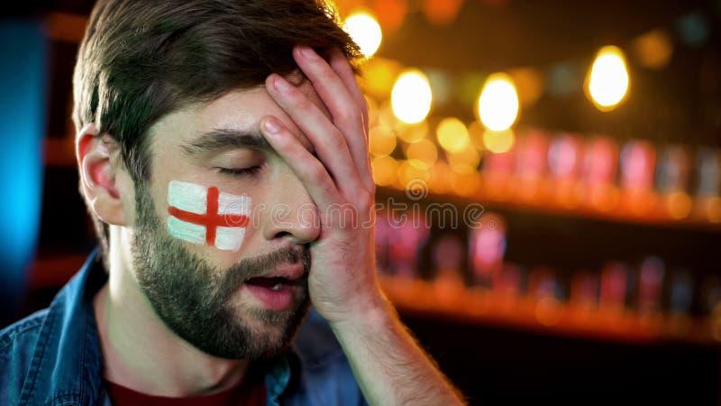 有英国旗子的生气的男性足球迷在做facepalm姿态的面颊 库存图片