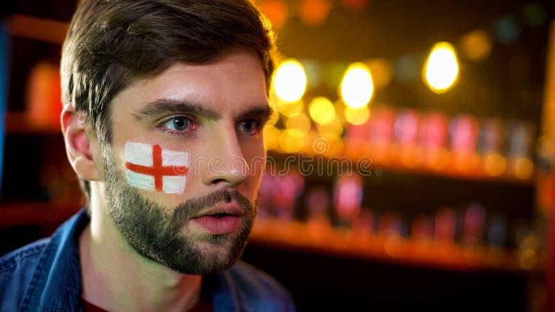 有英国的旗子的紧张的爱好者面颊的殷勤地观看体育比赛的 免版税库存照片