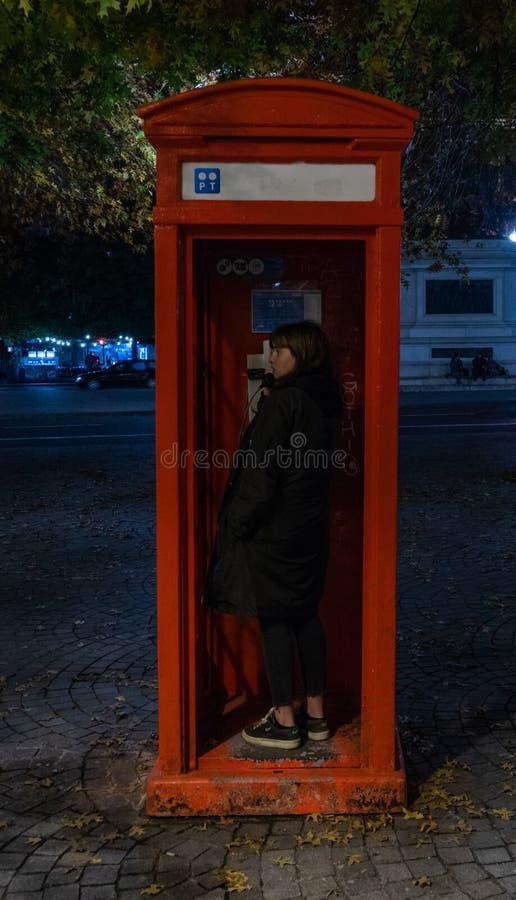 有英语女孩的typicall的电话箱子 免版税库存照片