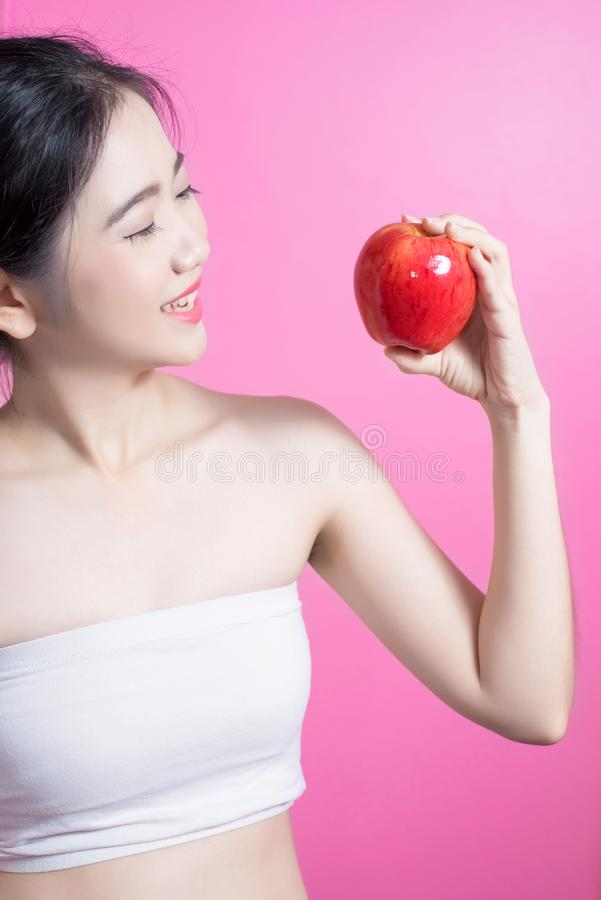有苹果概念的亚裔妇女 微笑和拿着苹果的她 秀丽面孔和自然构成 隔绝在桃红色背景 库存图片
