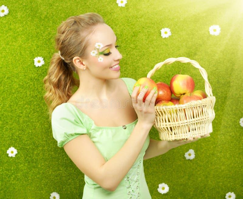 有苹果篮子的可爱的女孩  免版税库存照片