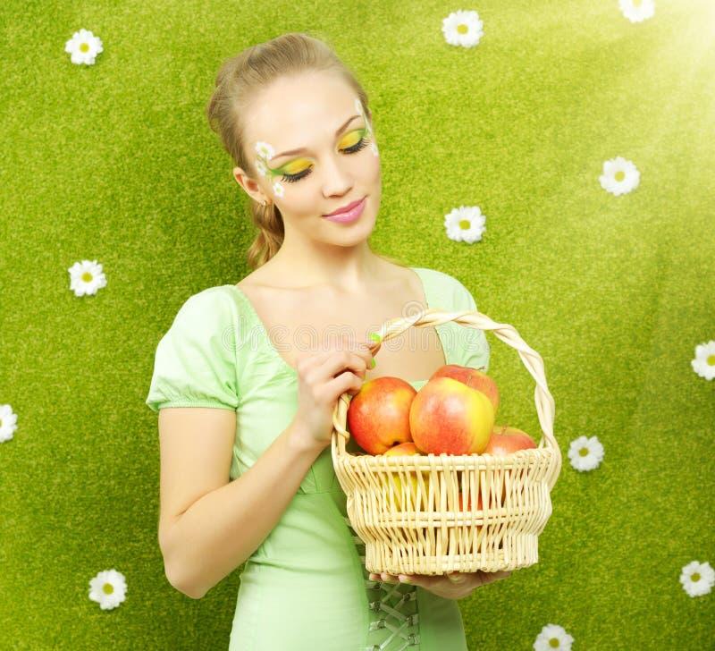 有苹果篮子的可爱的女孩  免版税图库摄影