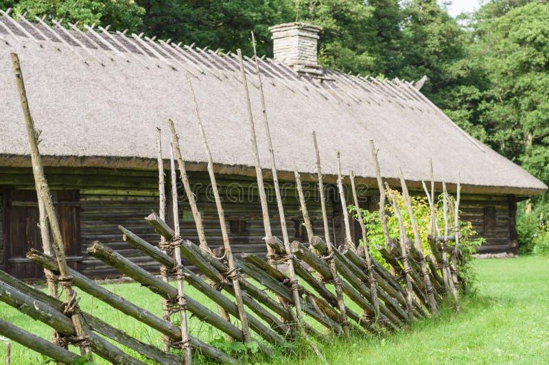 有茅屋顶和烟囱的老木房子 免版税库存照片