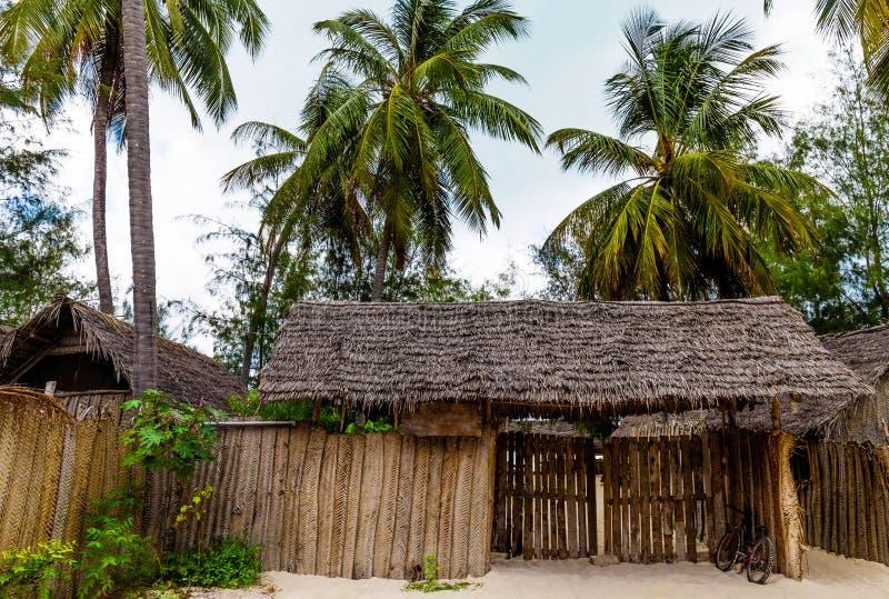 有茅屋顶和绿色棕榈树的亭子 免版税库存照片
