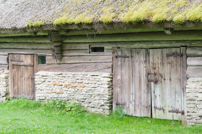 有茅草屋顶和两个门的老谷仓 免版税库存照片
