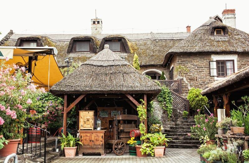 有茅草屋顶的庭院餐馆在匈牙利村庄,游人dest 免版税库存图片