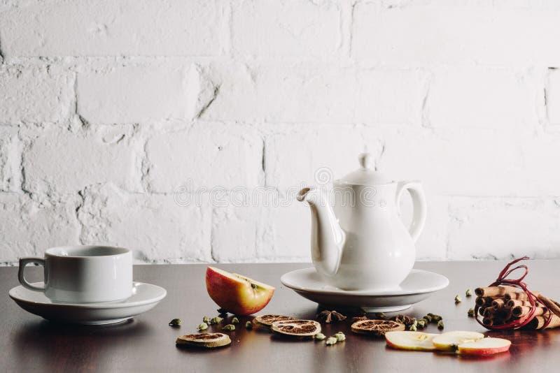 有茶壶的茶杯在老木桌上 库存图片