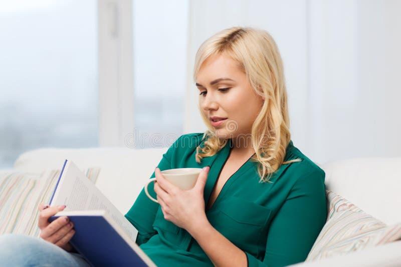 有茶杯阅读书的少妇在家 免版税图库摄影