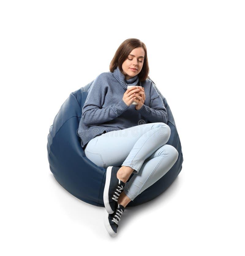 有茶的年轻女人坐装豆子小布袋椅子反对白色背景 免版税图库摄影